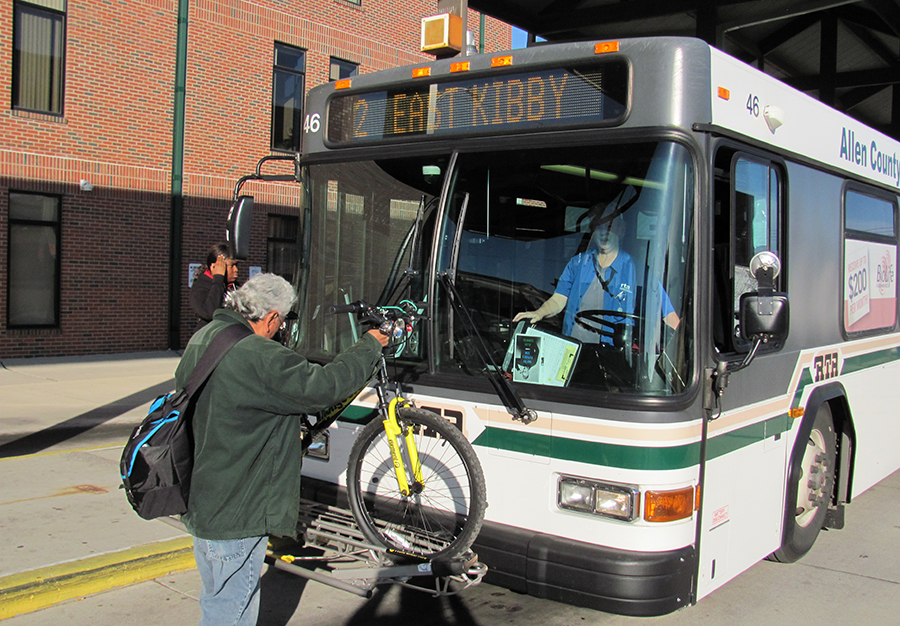 A man places a bike on the bike rack on the bus of the RTA. There are bike racks on all buses. If you need to ride the bus with a bike, read our bike policy.